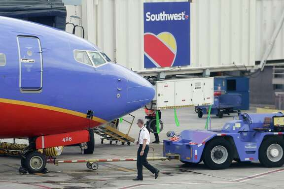 In this Monday, May 9, 2016, photo, a Southwest Airlines pilot performs a preflight check on an aircraft at Hartsfield–Jackson Atlanta International Airport, in Atlanta. Southwest Airlines reports financial results Wednesday, Oct. 26, 2016. (AP Photo/Mike Stewart)