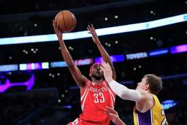 Houston Rockets forward Corey Brewer, left, shoots as Los Angeles Lakers center Timofey Mozgov, of Russia, defends during the first half of an NBA basketball game, Wednesday, Oct. 26, 2016, in Los Angeles. (AP Photo/Mark J. Terrill)