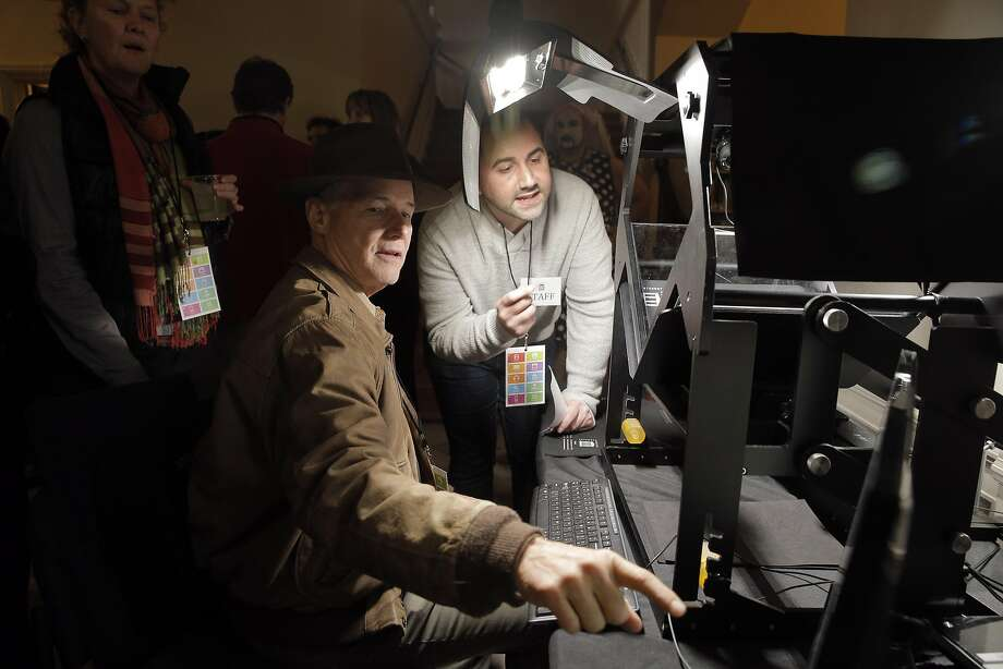 Larry Dieterich, left, checks out the tabletop scribe that digitized books demonstrated by Tim Bigelow, right, during the 20th anniversary celebration of the Internet Archive in San Francisco. Photo: Carlos Avila Gonzalez, The Chronicle