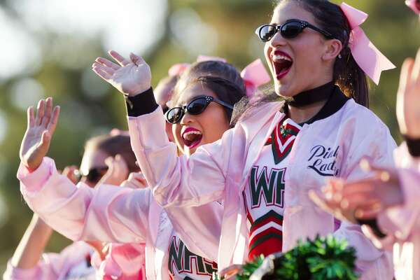 Cheerleaders wave to the crowd as they take part in The Woodlands High School's homecoming parade Wednesday, Oct. 26, 2016, in The Woodlands.