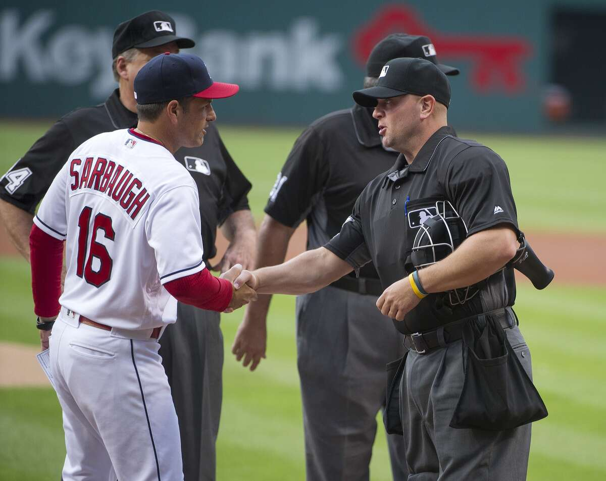 Cleveland Indians coach Mike Sarbaugh greets umpire Scott Barry before a baseball game in Cleveland, against the Oakland Athletics, Friday, July 29, 2016. (AP Photo/Phil Long)