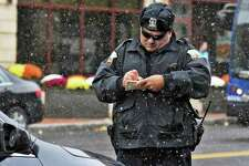 Police officer Nick Contompasis writes out a ticket on State Street as snow flurries begin Thursday Oct. 27, 2016 in Schenectady, NY. (John Carl D'Annibale / Times Union)