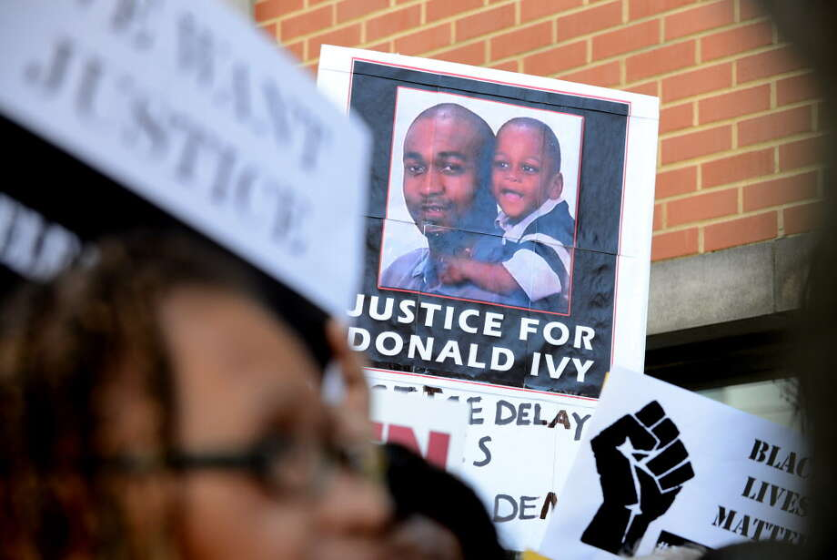 """Demonstrators hold signs in support of Marquis Dixon and """"Dontay"""" Ivy during a press conference and rally outside Albany District Attorney David Soares' office Monday, Aug. 10, 2015, in Albany, N.Y.  (Will Waldron/Times Union) ORG XMIT: MER2015081015344385 Photo: WILL WALDRON / 00032956A"""