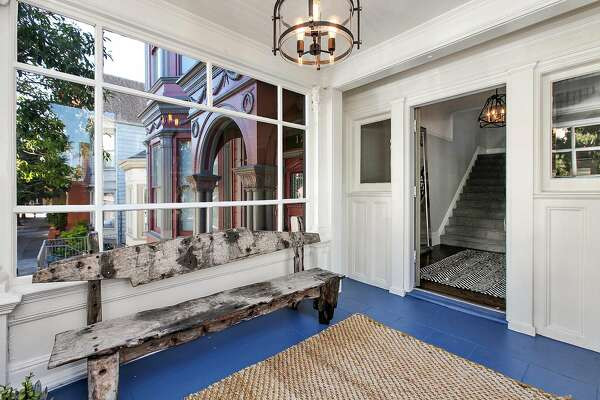 The Victorian's enclosed front porch captures sunlight through an oversized window.