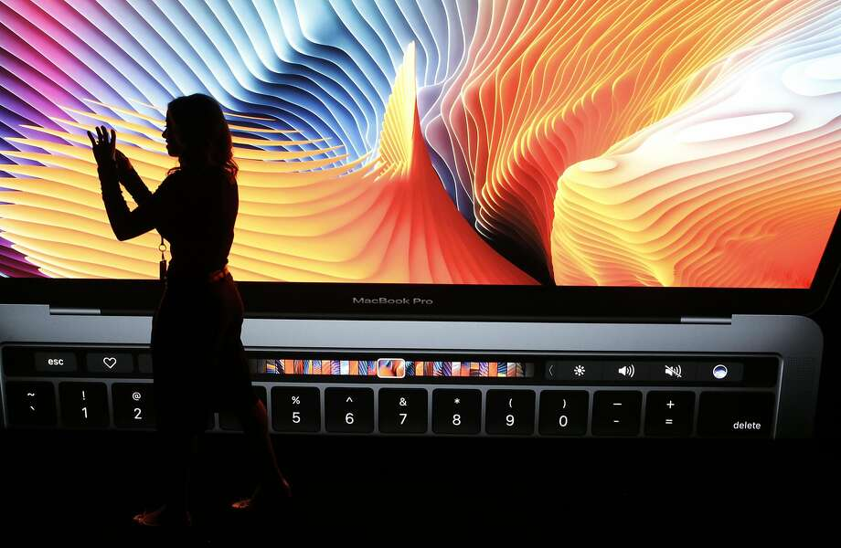 A visitor stands with a colorful image of an updated MacBook Pro at Apple head quarters, but British buyers may just see red. Photo: Paul Chinn, The Chronicle