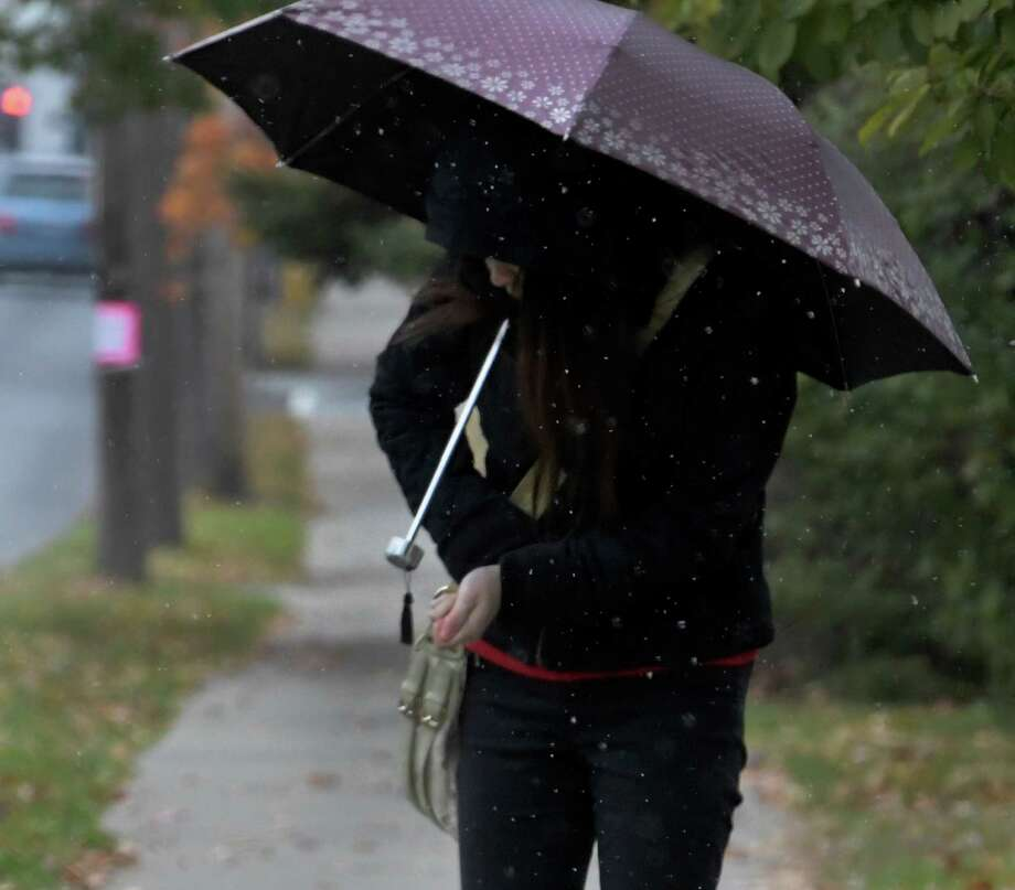 A commuter waits for a bus on Western Avenue as snow starts to fall during the forecast storm Thursday Oct. 27, 2016 in Albany, N.Y.  (Skip Dickstein/Times Union) Photo: SKIP DICKSTEIN