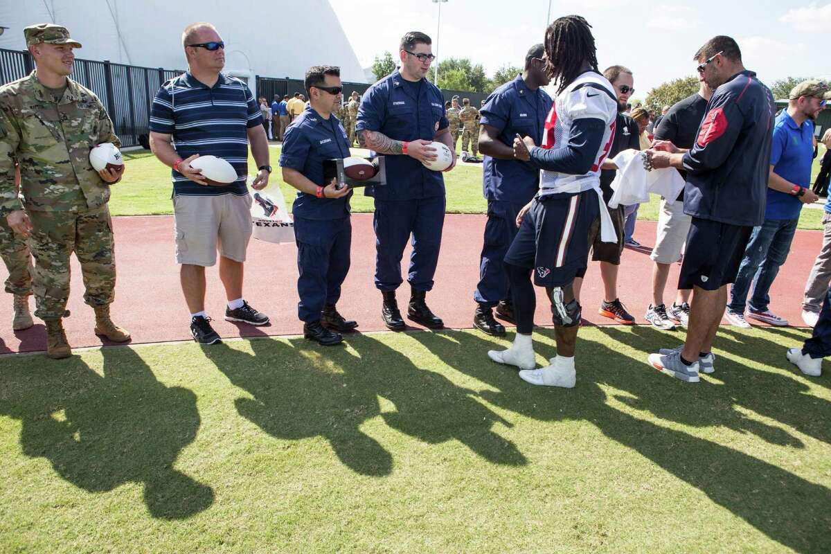 Houston Texans defensive back Lonnie Ballentine and linebackers coach Mike Vrabel sign autographs during the 10th Annual Salute to Service Miltary Barbecue at NRG Stadium on Thursday, Oct. 27, 2016, in Houston. The Texans hosted more than 200 service members, veterans from the USO, the Wounded Warrior Project and the Lone Star Veterans Assocation with a lunch, provided by HEB and cooked by the Battle Red Tailgate Crew. Following the lunch, they met with Texans players following practice.