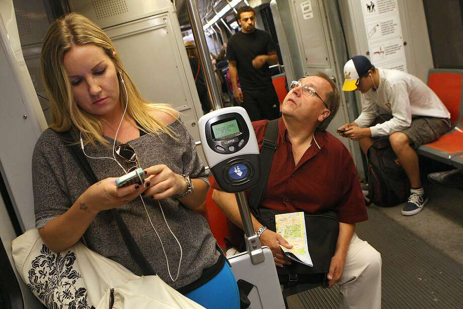Nova Pierce (left) from San Francisco on her cell phone while going to the gym on a Muni train heading outbound from the civic center station in San Francisco, California, on Friday, October 4, 2013. Photo: Liz Hafalia, The Chronicle