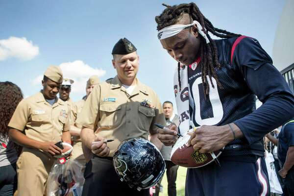 Houston Texans wide receiver DeAndre Hopkins (10) autographs a football for Petty Offier 1st Class SW Eric Stephens during the 10th Annual Salute to Service Miltary Barbecue at NRG Stadium on Thursday, Oct. 27, 2016, in Houston. The Texans hosted more than 200 service members, veterans from the USO, the Wounded Warrior Project and the Lone Star Veterans Assocation with a lunch, provided by HEB and cooked by the Battle Red Tailgate Crew. Following the lunch, they met with Texans players following practice.