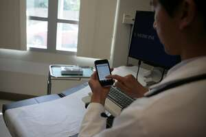 Dr. Steven Chang uses his the iPhone to access the application ePocrates in an exam room to receive updated drug information on August 5, 2008, Sacramento, Calif.   Dr. Steven Chang, resident in primary care at UC Davis Medical Center, is responsible for ePocrates being on Apple's iPhone list of applications. This application allows doctors to get updated information on drugs on Tuesday, August 5, 2008, Sacramento, Calif. Photo by Christina Izzo / The Chronicle