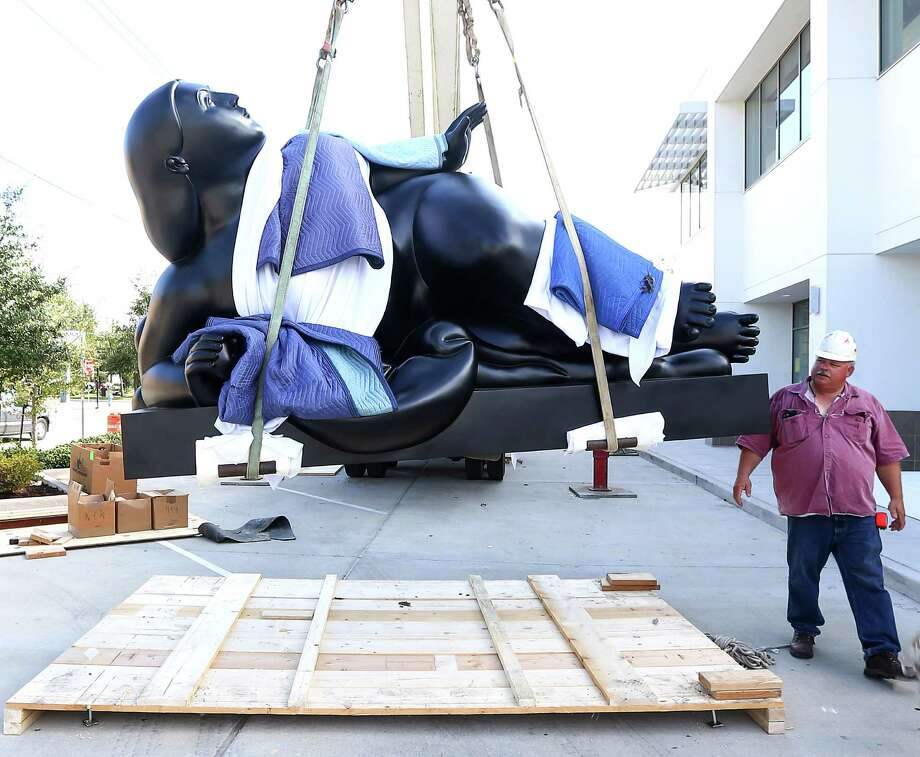 """The two-ton Fernando Botero sculpture """"Woman with Fruit"""" was hoisted into place at Art of the World Gallery on Monday. Photo: Jon Shapley, Houston Chronicle / © 2015  Houston Chronicle"""