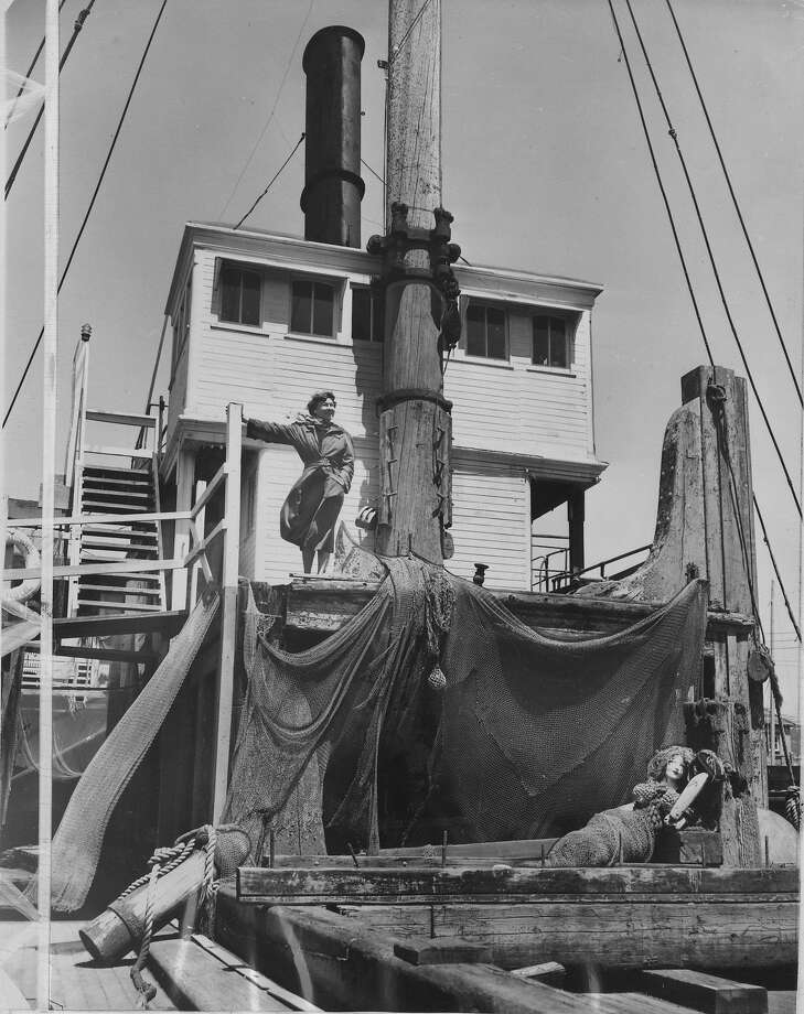 """Loyola Fourtane, creator of modern jewelry, surveys the harbor from the bridge of """"Lassen"""", lumber schooner converted into four artists' workshops. Her studio is up steps in wheelhouse, her sitting room in the captains cabin. 8/12/57 Photo: Bob Campbell, The Chronicle"""