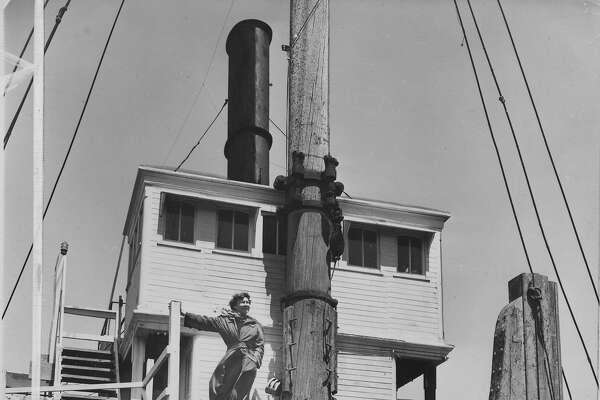 "Loyola Fourtane, creator of modern jewelry, surveys the harbor from the bridge of ""Lassen"", lumber schooner converted into four artists' workshops. Her studio is up steps in wheelhouse, her sitting room in the captains cabin. 8/12/57"