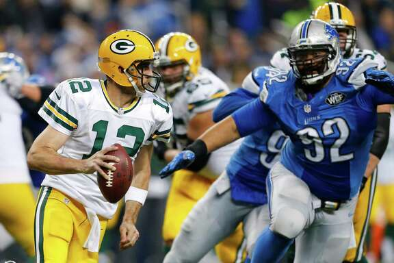 Green Bay Packers quarterback Aaron Rodgers (12) scrambles away from Detroit Lions defensive tackle Haloti Ngata (92) during the second half of an NFL football game, Thursday, Dec. 3, 2015, in Detroit. (AP Photo/Rick Osentoski)