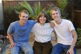 This Dec. 25, 2012, photo taken by Andrew Wiegardt, left, shows him with his brother, Nick Wiegardt as they pose with their mother, Kirsten Englund. Three years ago, Jeffrey Boyce shot and killed Englund at a scenic overlook on the Oregon coast, using one of three weapons purchased by his mother. Boyce's mother has agreed to pay $400,000 to Englund's family and to assist them in their lawsuit against two gun dealers. (Andrew Wiegardt via AP)