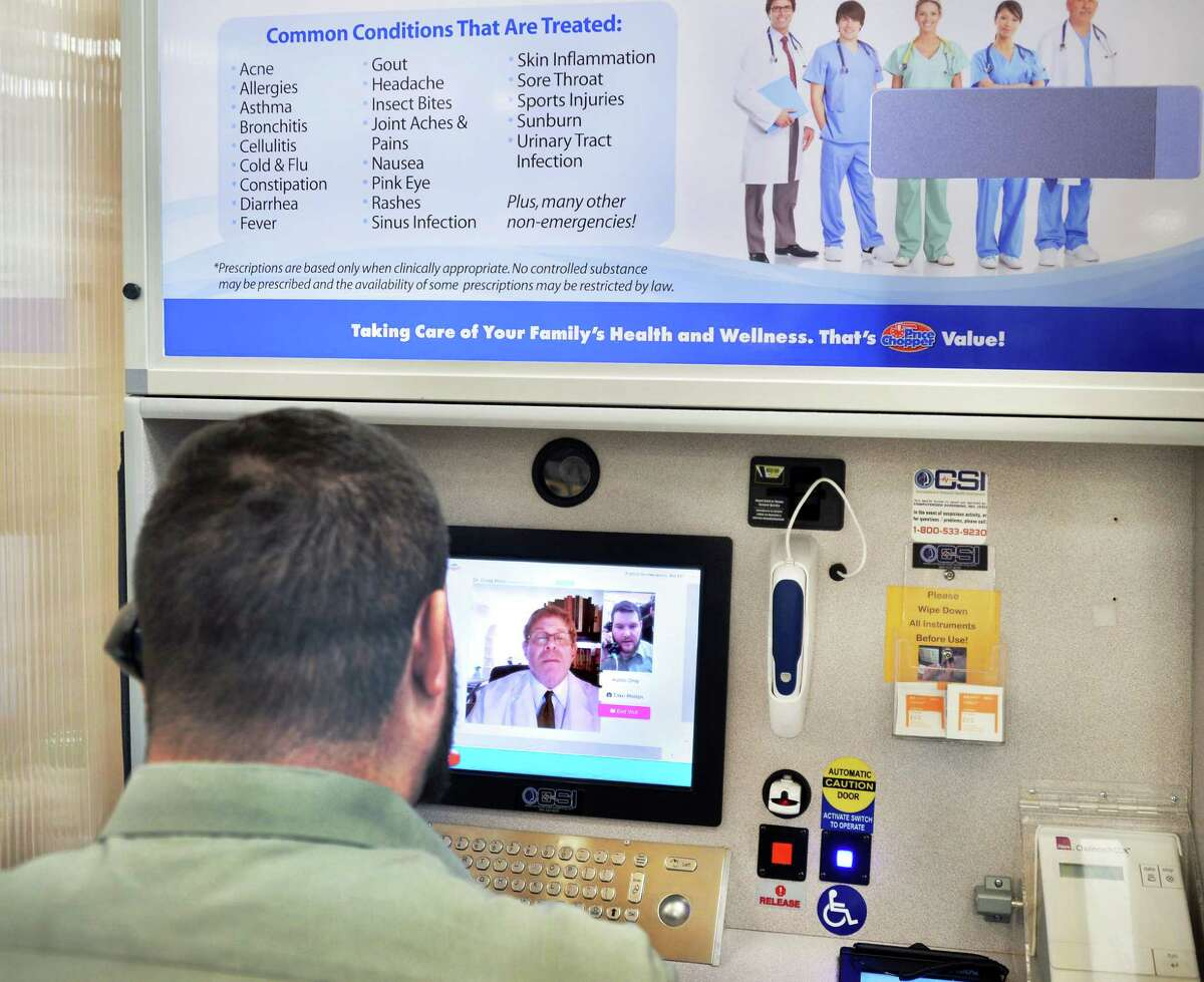 """Store pharmacist Michael Zappone, left, speaks with Dr. Craig Price of New Jersey during a demonstration of a new telemedicine option """"Doctor on Demand"""", at the Glenmont Price Chopper Thursday Jan. 28, 2016 in Glenmont, NY. (John Carl D'Annibale / Times Union)"""