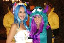 WOAI anchorwoman Delaine Mathieu (right) would fit right in on Sesame Street in this bright fuzzy Halloween concoction. Her pal (left) went as a unicorn.