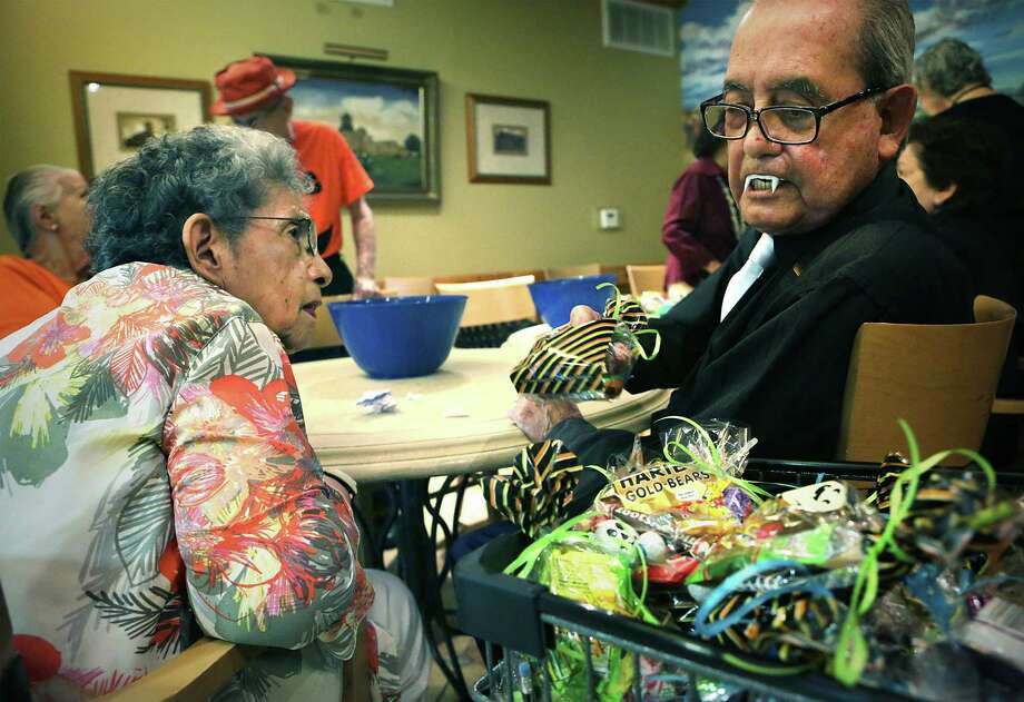Santos Venzor, left, whose birthday is on Halloween, checks out Gerry Garcia's teeth as they and other residents of Villa de San Antonio gathered the past two days to fill trick-or-treat bags with candy to be delivered to the Children's Shelter,  on Wednesday, Oct. 26, 2016. Photo: Bob Owen, Staff / San Antonio Express-News / ©2016 San Antonio Express-News