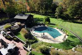 The backyard of a home currently on the market on Farms Rd. in north Stamford, Conn. has an inground pool, a pool house/ guest house and acres of protected property.