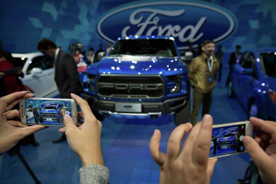 FILE - In this April 23, 2016, file photo, attendees take photos of a Ford F-150 Raptor pickup truck by smartphones at a promotional event for Ford ahead of the biennial Auto China car show in Beijing. Ford Motor Co. reports financial results Thursday, Oct. 27, 2016. (AP Photo/Mark Schiefelbein, File) Photo: Mark Schiefelbein, STF / Copyright 2016 The Associated Press. All rights reserved. This material may not be published, broadcast, rewritten or redistribu