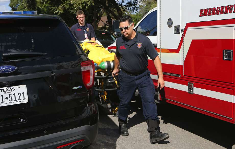 Emergency personnel transport a patient at the Whis- pering Heights Apartments after a police officer shot a man who police say had wielded a rifle. Photo: John Davenport / San Antonio Express-News / ©San Antonio Express-News/John Davenport