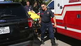 Emergency personnel transport a patient at the Whis- pering Heights Apartments after a police officer shot a man who police say had wielded a rifle.