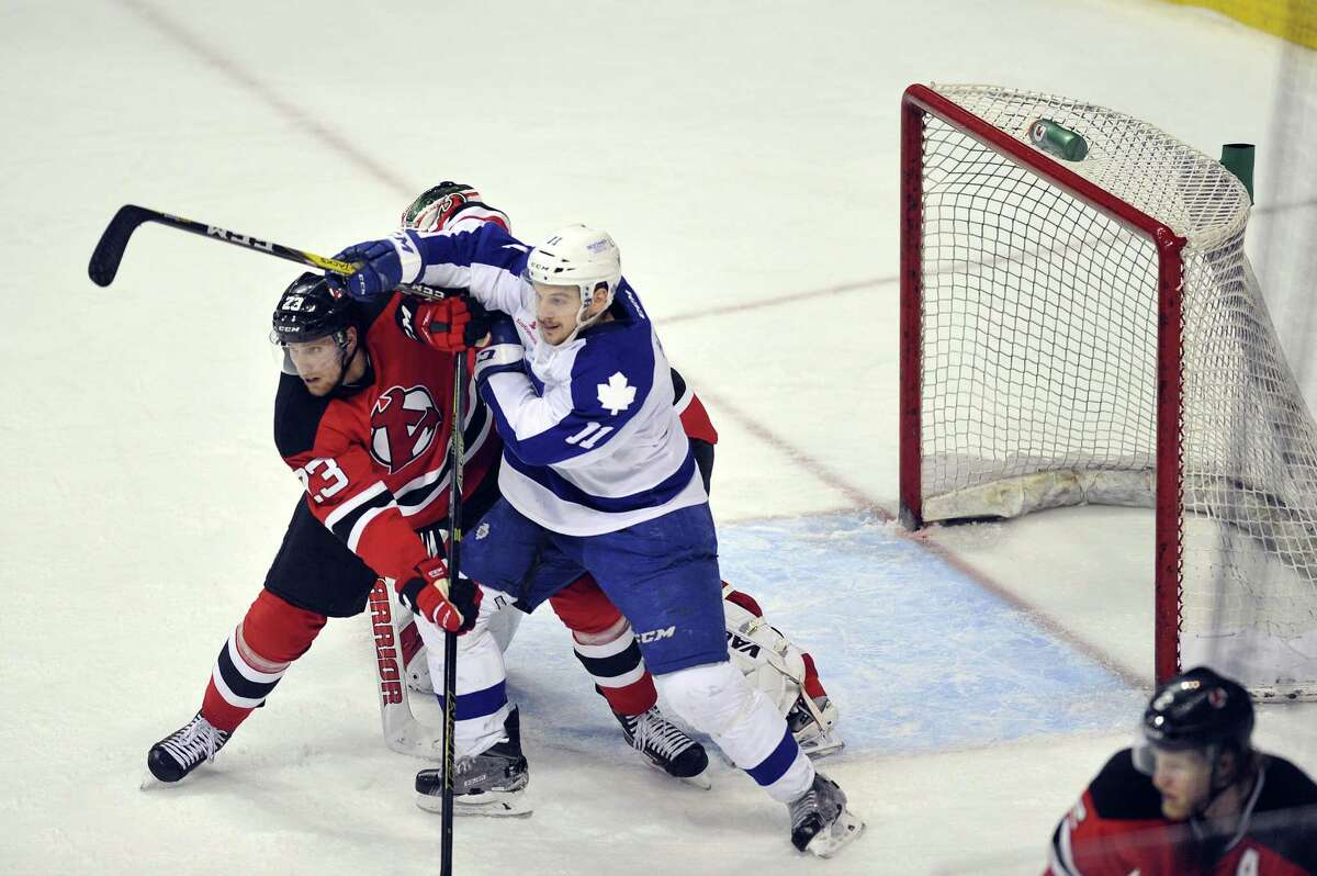 Vojtech Mozik of the Albany Devils, left, and Zach Hyman of the Toronto Marlies fight for position in front of the net during their American Hockey League quarterfinal playoff series game on Sunday, May 8, 2016, in Albany, N.Y. (Paul Buckowski / Times Union) ORG XMIT: MER2016102715314314