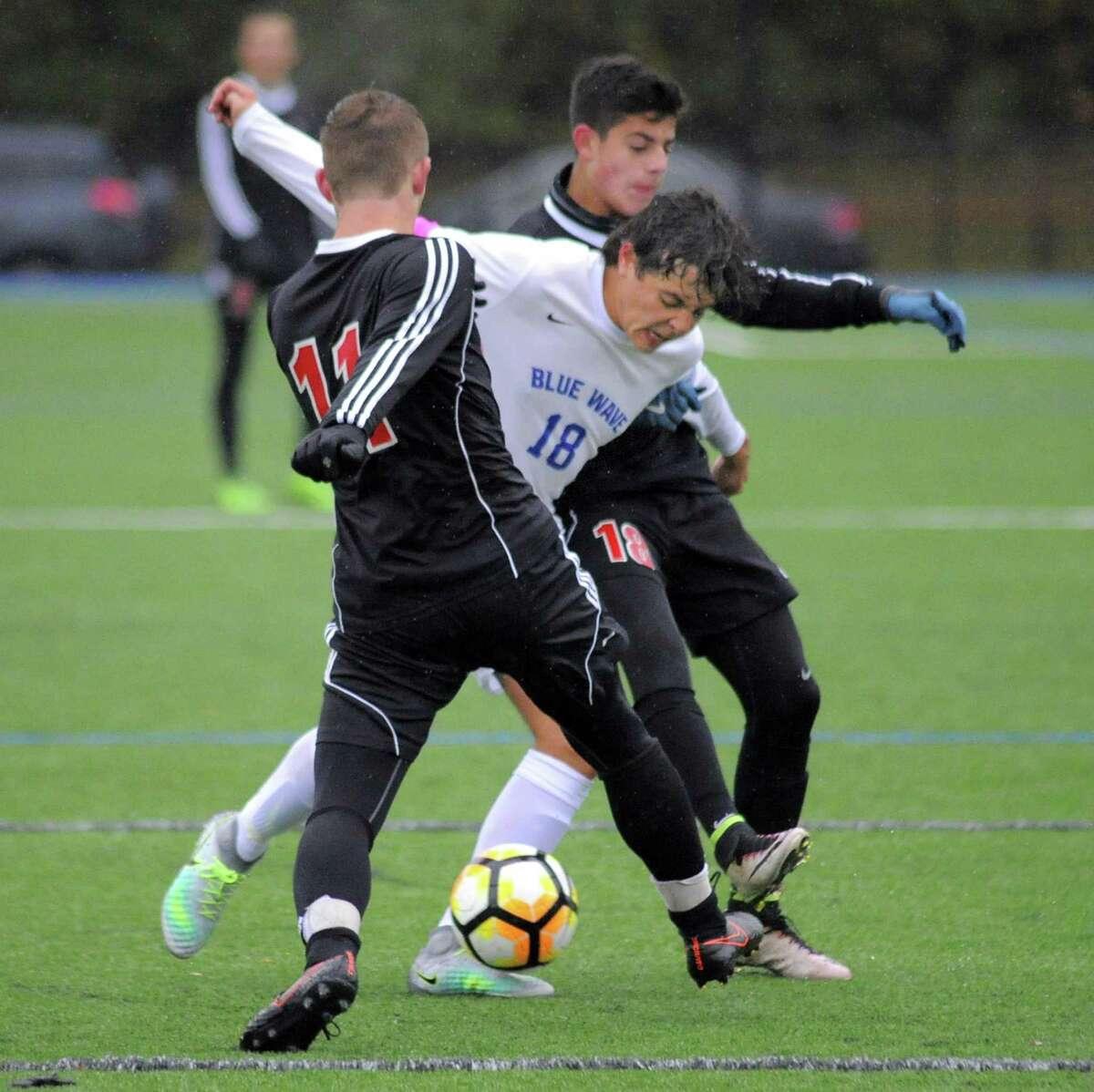 Darien Pablo Martinez splits Fairfield Warde defenders David Harvey and Lucas Montero in a FCIAC Boys Soccer Quarterfinal game in Darien, Conn. on Thursday, Oct. 27, 2016.