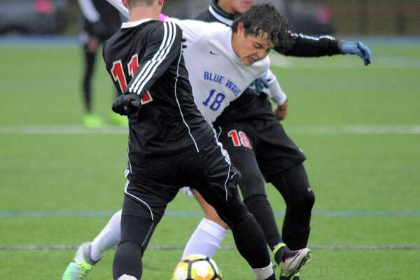 Darien Pablo Martinez splits Fairfield Warde defenders David Harvey and Lucas Montero in a FCIAC Boys Soccer Quarterfinal game in Darien, Conn. on Thursday, Oct. 27, 2016.