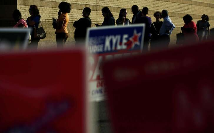 Hundreds waited in line to vote at Fiesta Mart off Kirby Drive during the first day of early voting Monday.