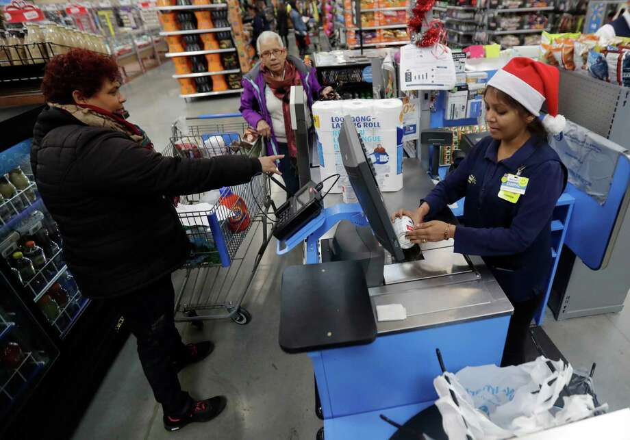 In this Wednesday, Oct. 26, 2016, photo, Gladys Ortega, left, and Ursula Polano, center, both from Paterson, N.J., check out at the register of Dimpal Mandania, at Wal-Mart in Teterboro, N.J. Wal-Mart may be known for its every low prices but this holiday season it wants to be known for service too. (AP Photo/Julio Cortez) ORG XMIT: NJJC402 Photo: Julio Cortez / Copyright 2016 The Associated Press. All rights reserved.