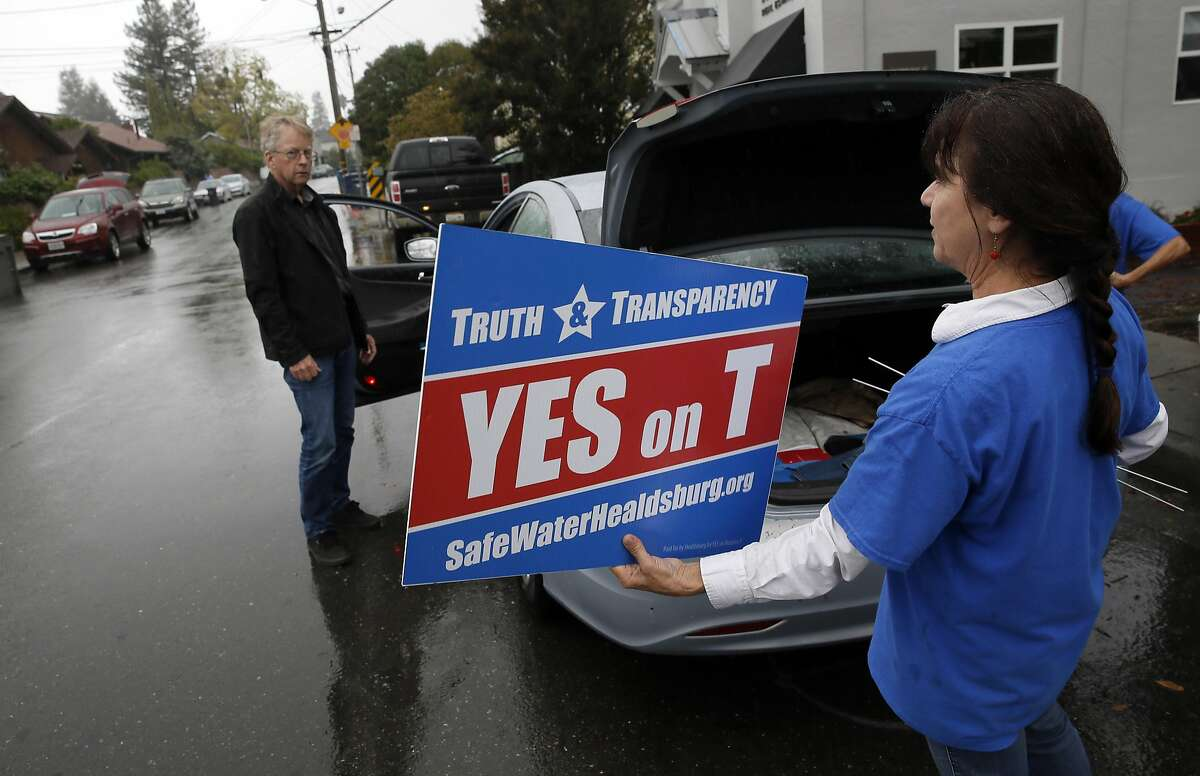 Yes on Measure T supporter Dawna Gallagher Stroeh hands over a sign to resident Hampton Bynum as she and Jeanie Rudd, (right behind) canvas a neighborhood in Healdsburg, California on Thursday October 27, 2016.