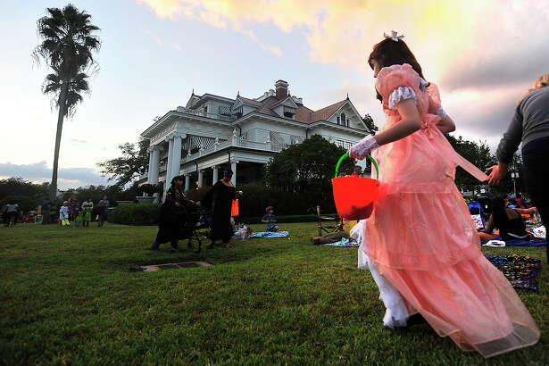 """Children make their way through the grounds collecting treats during the annual Fall Picnic held on the grounds of the McFaddin-Ward House Thursday. Attendees were encouraged to dress up and bring candy to share for the Halloween-themed event. An outdoor showing of """"Monster House,"""" music by Katy Whitney and the Draw, art on the porch by Ines Alvidres, games, and a first floor house tour were among the highlights of the popular, free community event. Photo taken Thursday, October 27, 2016 Kim Brent/The Enterprise"""