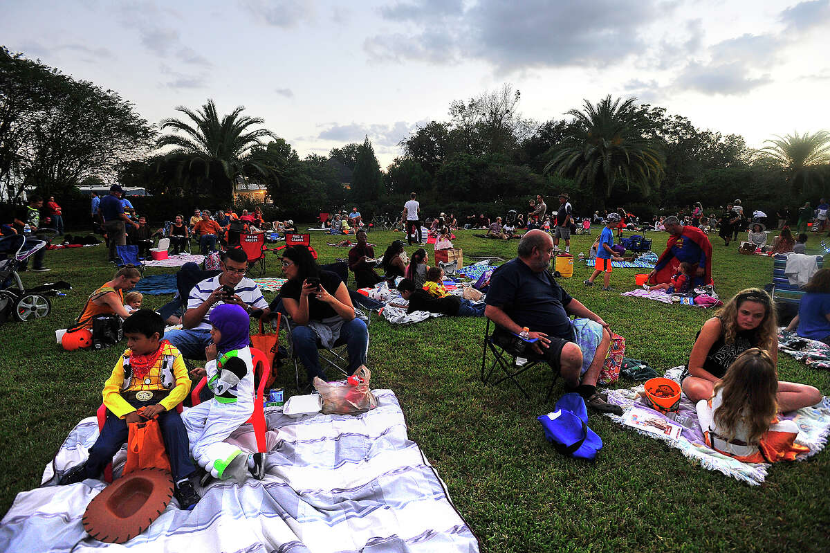 Families enjoy the festivities during the annual Fall Picnic held on the grounds of the McFaddin-Ward House Thursday. Attendees were encouraged to dress up and bring candy to share for the Halloween-themed event. An outdoor showing of