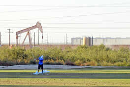 A golfer practices with a pumpjack visible in the background at Midland Country Club, Thursday, Oct. 27, 2016. James Durbin/Reporter-Telegram