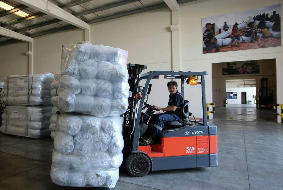 A lift truck driver uploads family tents for the Mosul refugees at the UNHCR warehouses, part of the International Humanitarian City (IHC) in Dubai, United Arab Emirates, Thursday, Oct. 27, 2016. The United Nations' refugee agency is shipping tents, blankets and other aid from the United Arab Emirates to northern Iraq to help those affected by the U.S.-led push to retake Mosul from the Islamic State group. (AP Photo/Kamran Jebreili) ORG XMIT: XKJ101 Photo: Kamran Jebreili / Copyright 2016 The Associated Press. All rights reserved.