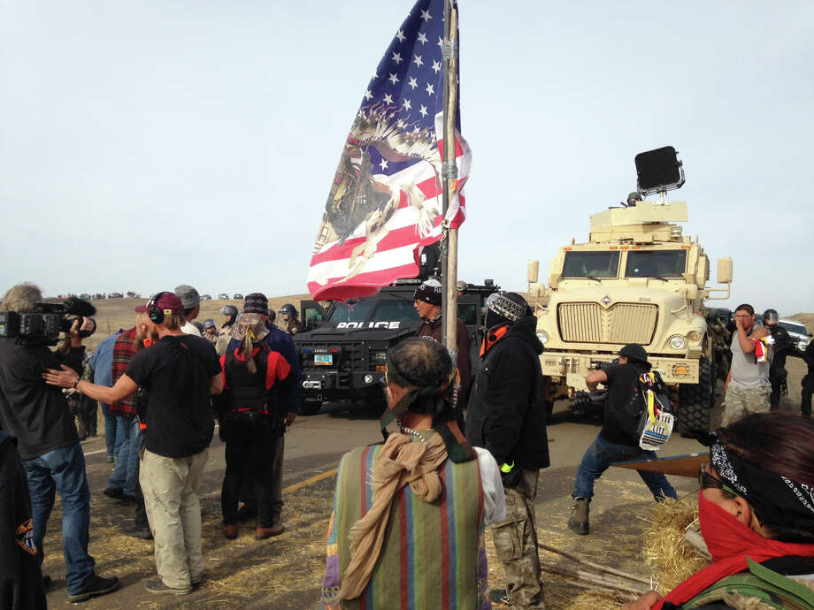 Dakota Access pipeline protesters defy law enforcement officers who are trying to force them from a camp on private land in the path of pipeline construction on Thursday, Oct. 27, 2016, near Cannon Ball, N.D. The months-long dispute over the four-state, $3.8 billion pipeline reached a crisis point when the protesters set up camp on land owned by pipeline developer Energy Transfer Partners. The disputed area is just to the north of a more permanent and larger encampment on federally-owned land where hundreds of protesters have camped for months. (AP Photo/James MacPherson) ORG XMIT: RPJM102 Photo: James MacPherson / Copyright 2016 The Associated Press. All rights reserved.