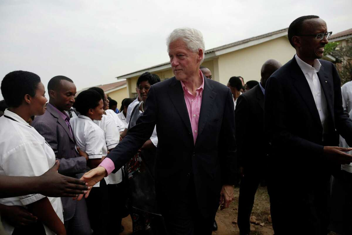 Former U.S. President Bill Clinton and Rwandan President Paul Kagame, right, greet medical students at an event in Kigali, Rwanda, July 19, 2012. A recent tour of several African countries gave Clinton, his daughter Chelsea, and a handful of donors and aides a first-hand look at the philanthropic work of the Clinton Foundation. (Ed Ou/The New York TImes)
