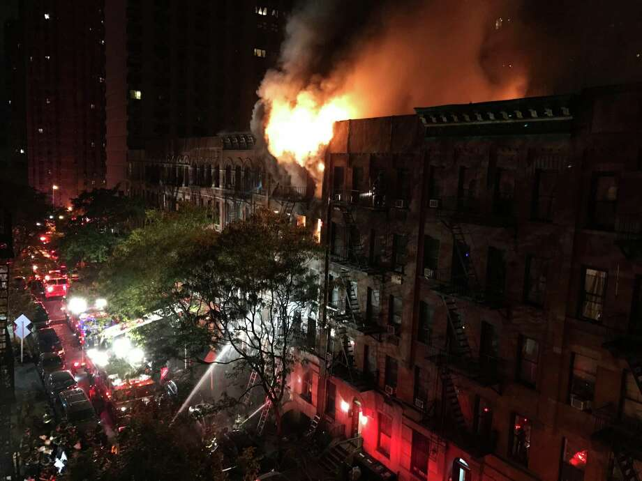 Firefighters work to put out a blaze at an apartment building on the Upper East Side in New York on Thursday, Oct. 27, 2016. The flames quickly spread throughout the building and were shooting out the roof at one point, sending burning embers onto nearby buildings. (Matt Bonaccorso via AP) ORG XMIT: NY110 Photo: Matt Bonaccorso / Matt Bonaccorso