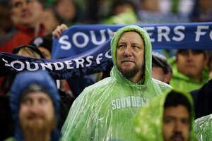 Fans wait in the rain for the Western Conference Knockout Round playoff game between the Seattle Sounders FC and Sporting Kansas City, Thursday, Oct. 27, 2016.