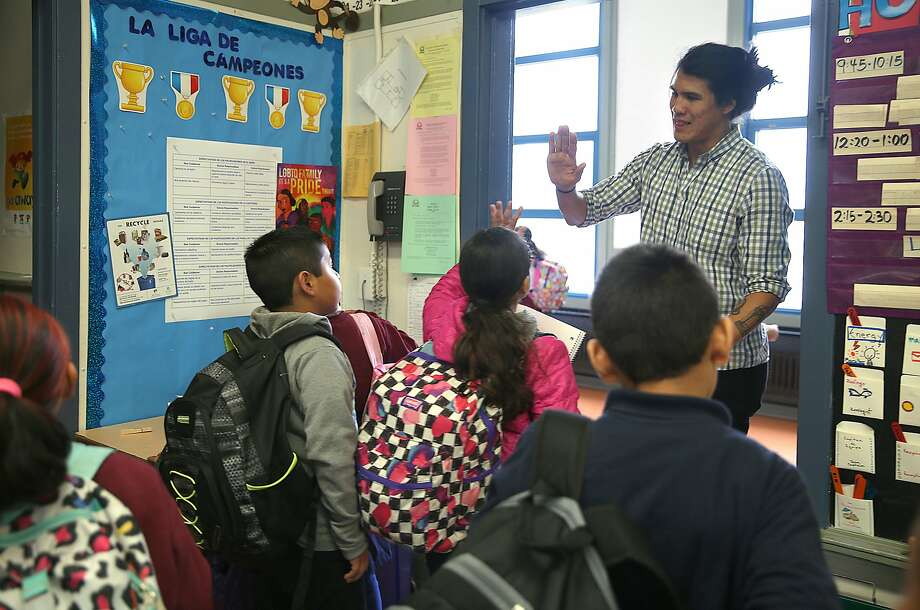 Cleveland Elementary School teacher Fernando Che high-fives his morning class of third graders. Teachers like Che can use a new version of the state's 403bcompare.com website to learn about retirement savings plans. Photo: Liz Hafalia, The Chronicle