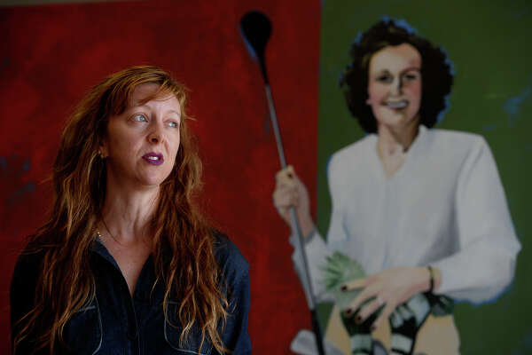 Summer Lydick speaks about her paintings that now hang at the Jack Brooks Regional Airport on Thursday. The three paintings feature famous locals, such as Bum Phillips, George Jones and Bubba Smith.  Photo taken Thursday 10/27/16 Ryan Pelham/The Enterprise