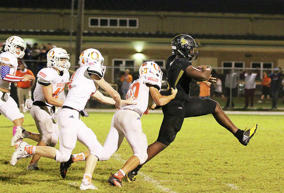 Tyris Williams scampers down the field with Bobcats in pursuit. Liberty picked up their first win against Orangefield in the last four years. Photo: David Taylor