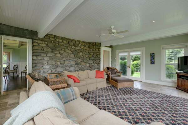 A later addition houses the family room, which functions as a sunroom with a tumbled limestone radiant heated floor, walls of floor-to-ceiling windows, and French doors; one leads to the pool and the other to a long covered porch.