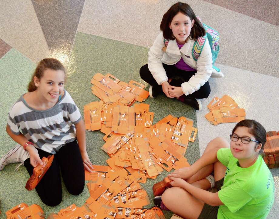Middlesex Middle School sixth-graders Sarah Jackson, Reagan Dineen and Lauren LaJaunie put together boxes as part of their Trick-or-Treat for UNICEF coin drive. Photo: Contributed Photo