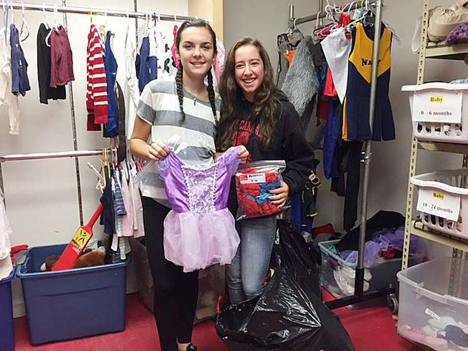 Alexandra Budnick and Ryan Benevento show off some of the outfits donated to their nonprofit, Community Costumes, which gives costumes to families in need. Photo: Heather Budnick / Contributed Photo / New Canaan News
