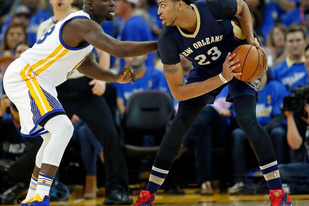 Golden State Warriors' Draymond Green defends New Orleans Pelicans' Anthony Davis in 1st quarter during NBA game at Oracle Arena in Oakland, Calif., on Tuesday, October 27, 2015.