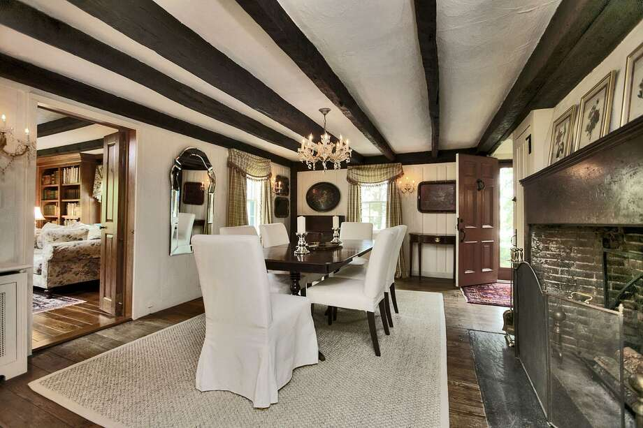The formal dining room of this 18th century colonial has a large fireplace that contains a bread oven and storage cabinet built into the mantel suggesting this was probably the original kitchen. Photo: Contributed / Contributed Photo / Westport News