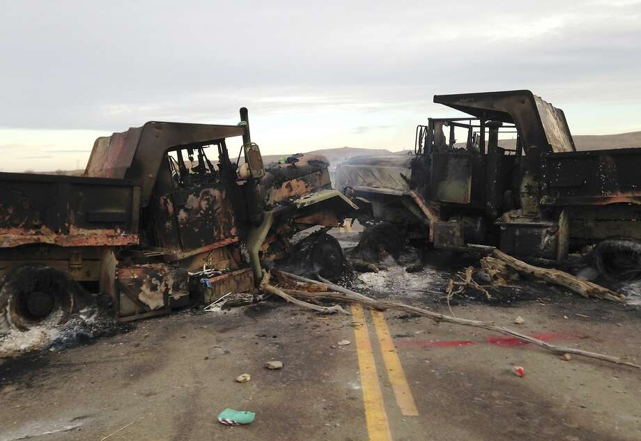 The burned hulks of heavy trucks block Highway 1806 near Cannon Ball, N.D., near where protesters of an oil pipeline were evicted from private property. Photo: James MacPherson, Associated Press