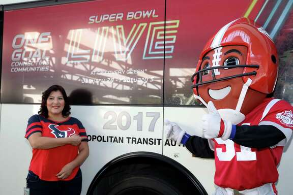 Marcy Suarez, Super Bowl volunteer and Metropolitan Transit Authority of Harris County employee, gets her photographs taken with Houston Super Bowl Host Committee official mascot, TD, next to the METRO Super Bowl-branded bus Friday, Oct. 28, 2016, in Houston. METRO would be expanding their services during the period of Super Bowl to transport the greater volume of people.